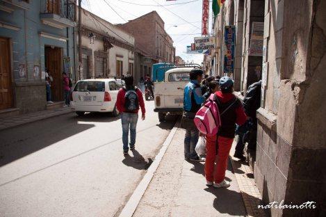 Gente caminando por la calle, por el auto estacionado arriba de la vereda.